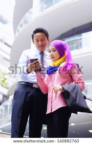 Two young executives looking at tablet phone outdoor