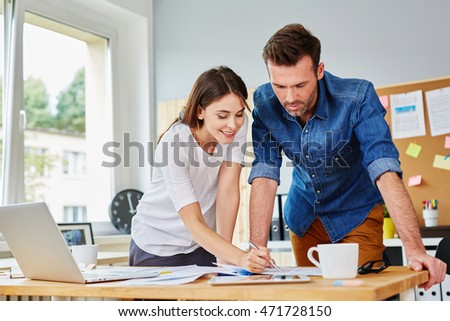 Two young executives working at office