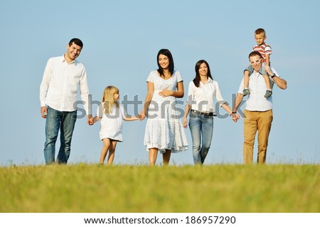 Two young families with kids walking on beautiful summer meadow enjoying and having fun - stock photo