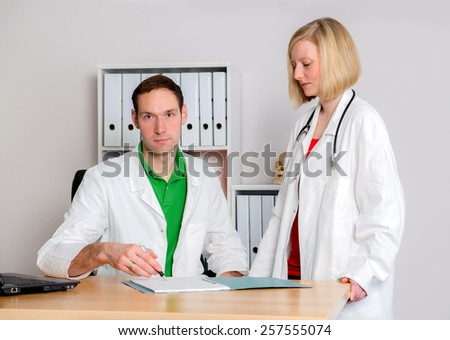 two young  family doctor in her office woking together
