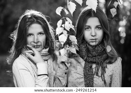 Two young fashion teen girls in autumn forest