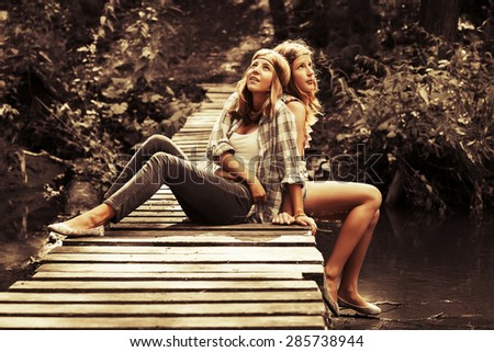 Two young fashion teen girls sitting on the bridge in a summer forest - stock photo