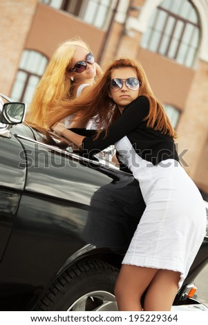 Two young fashion women at the retro car - stock photo