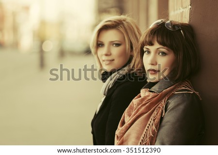 Two young fashion women on the city street - stock photo