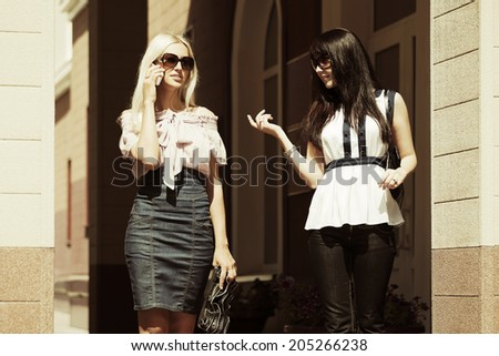 Two young fashion women walking on the city street  - stock photo