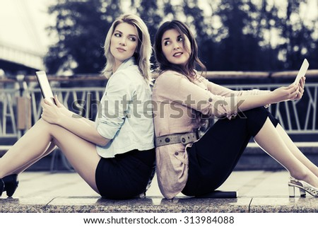 Two young fashion women with a digital tablet computers - stock photo