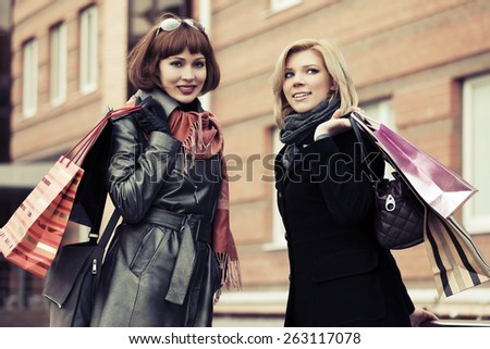 Two young fashion women with shopping bags  - stock photo