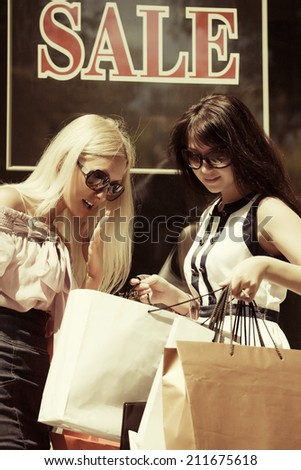 Two young fashion women with shopping bags at the mall windows  - stock photo