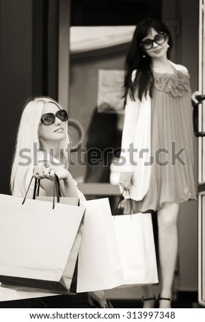 Two young fashion women with shopping bags next to mall window - stock photo