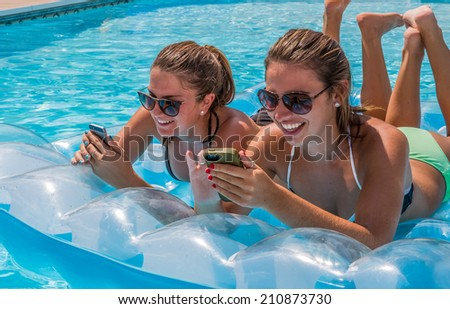 Two young female adults lying on raft in swimming pool checking their cell phones and having fun during summer. - stock photo