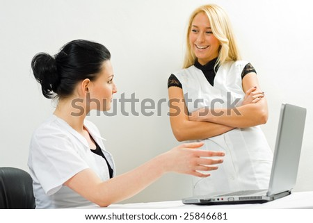 Two young female doctors, talking, the older one explaining something to the younger, using a laptop - part of a series. - stock photo