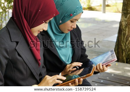 Two young female executive using tablet touchscreen outdoor - stock photo