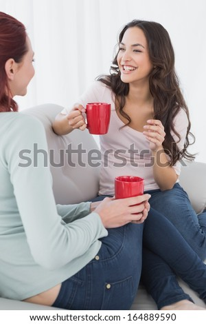 Two young female friends enjoying a chat with red coffee cups in the living room at home - stock photo