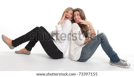 Two young female friends happily exchanging confidences - stock photo