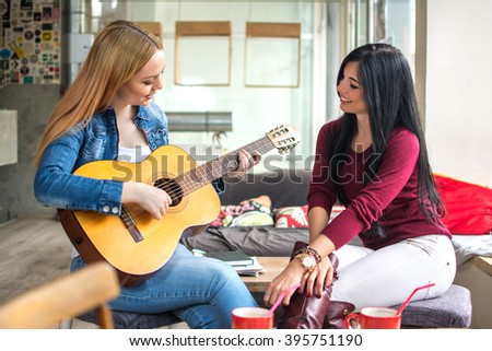 Two young female friends having fun in cafe. One girl playing guitar and the other one listening. - stock photo