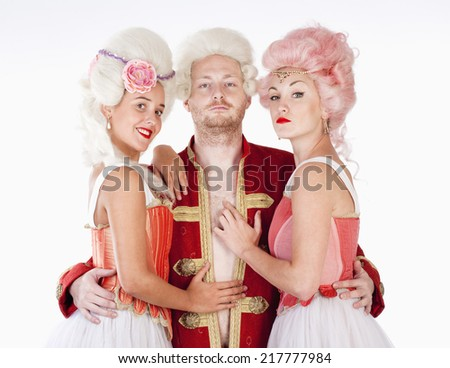 Two Young Female Friends in Historical Costumes Embracing a Man - stock photo