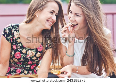 Two young female friends laugh and eat chocolate outdoors  - stock photo