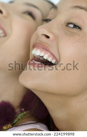 Two young female friends laughing, one looking at camera, extreme close-up of faces, cropped - stock photo
