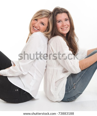 Two young female friends leaning on each other - stock photo