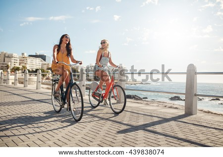 Two young female friends riding their bicycles on the seaside promenade. Cheerful young women riding bikes at the waterfront on a summer day. - stock photo