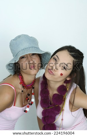 Two young female friends wearing lots of accessories, puckering at camera, portrait - stock photo