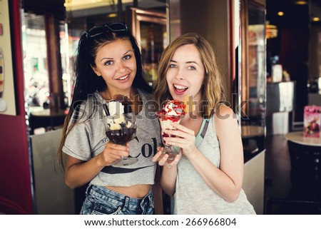Two young female multiracial girl friends laugh and eat dessert in cafe outdoor - stock photo