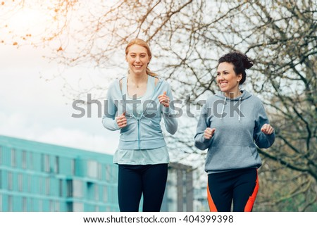 Two young female running together in city environment