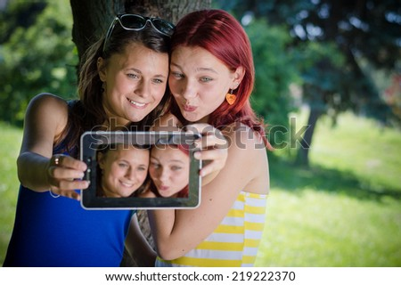 Two young female students sitting in park with tablet pc - stock photo