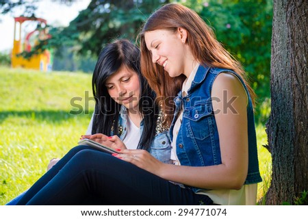 Two young female students sitting in park with tablet pc or mobile phone - stock photo