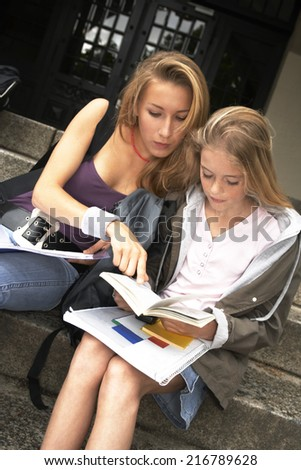Two young female students studying on the steps. - stock photo
