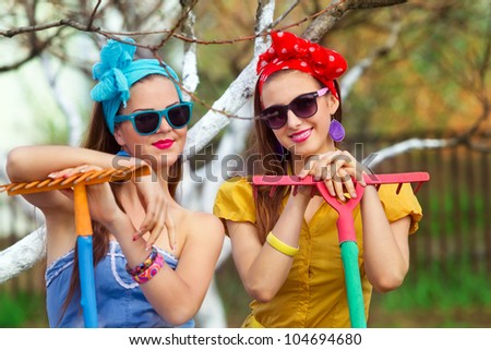 Two young female with rakes on garden