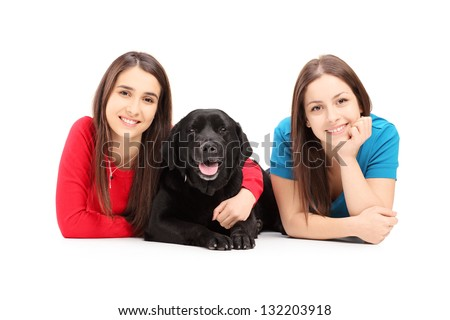 Two young females lying and posing with a dog isolated on white background - stock photo