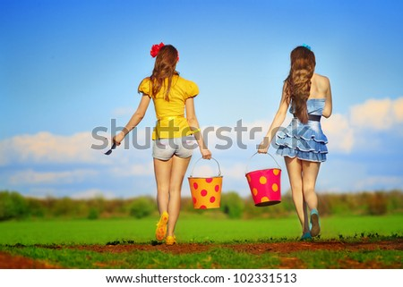 Two young females walking with  buckets on garden