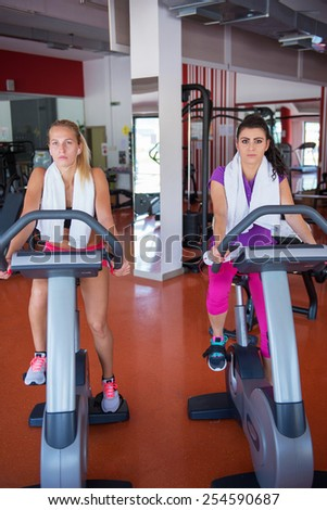 two young fit woman doing sport spinning in the gym