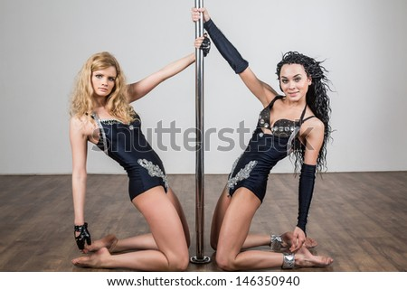 Two young flexible dancer dancing with a pole