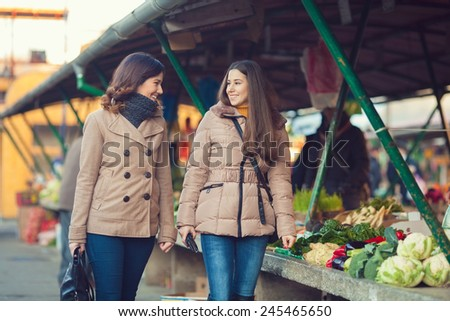 Two young friends at farmer's market looking for organic groceries - stock photo