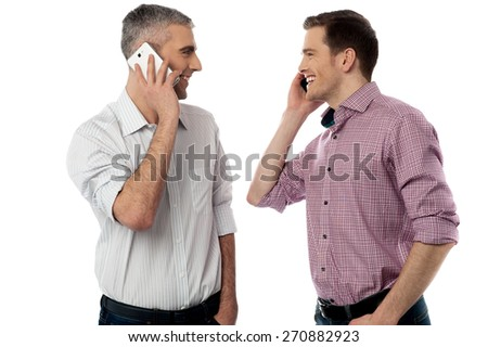 Two young friends happily talking on mobile phone