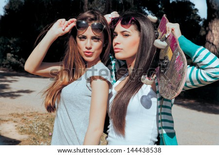two young friends holding a skateboard and sending a kisses . Summer style pictures. - stock photo