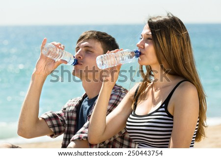Two young friends relaxing on the coast and drinking  bottled water - stock photo
