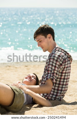 Two young friends sitting on the sand at the beach a summer day - stock photo