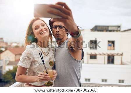 Two young friends taking a selfie on rooftop. Man holding smart phone and taking self portrait with woman holding a cocktail during a party. - stock photo