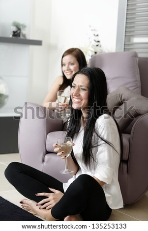 Two young friends watching television at home.