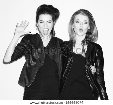 Two young girl friends having fun and jumping together. Brunette giving five her hand. Blonde making surprised face. Both looking at camera. Inside - stock photo