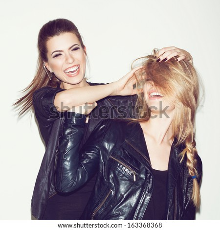 Two young girl friends having fun and smiling. Brunette making hairdo to blonde - stock photo