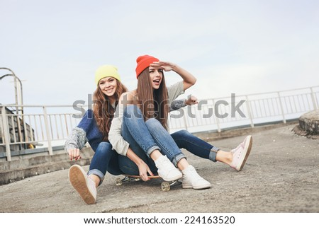 Two young  girl friends having fun. Downhill, longboarding . Outdoors, lifestyle. - stock photo