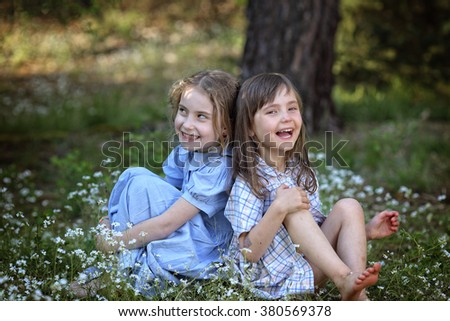 Two young girl friends laughing on the meadow - stock photo