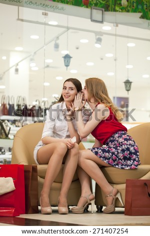 Two young girl friends sitting in the shop and relax after shopping - stock photo