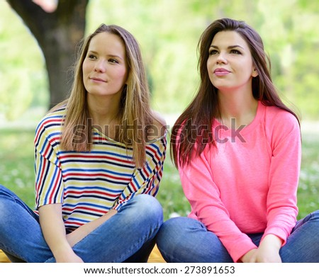 Two young girl friends sitting on grass at summer day