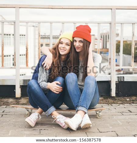 Two young girl friends sitting together on long-board and having fun. Outdoors, lifestyle. - stock photo