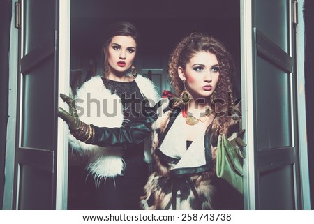 Two young girl friends standing together and having fun. Looking at camera. Inside club fashion vintage style  - stock photo